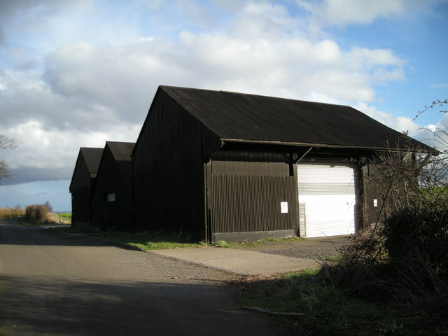 Big black shed beside a narrow lane