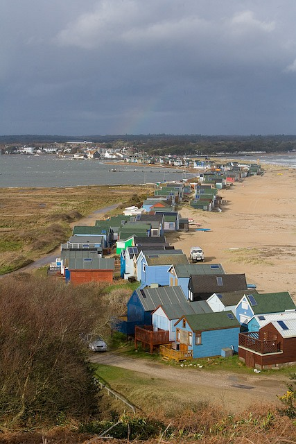 Beach huts on Muddeford Spit in stormy weather