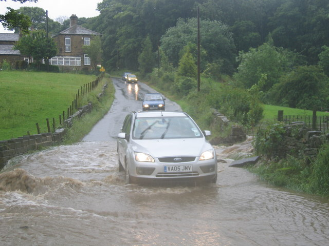 Cars driving through flooded lane in Flockton