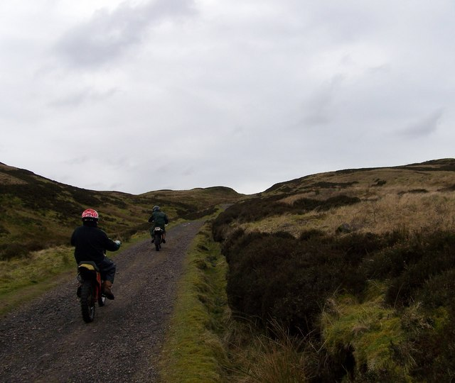 Two motor bikes climbing the hill towards Loch Thom