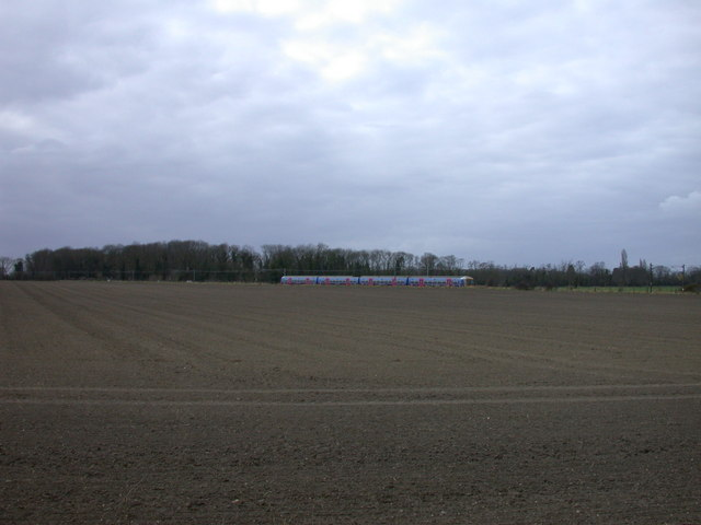 Bare field with distant train