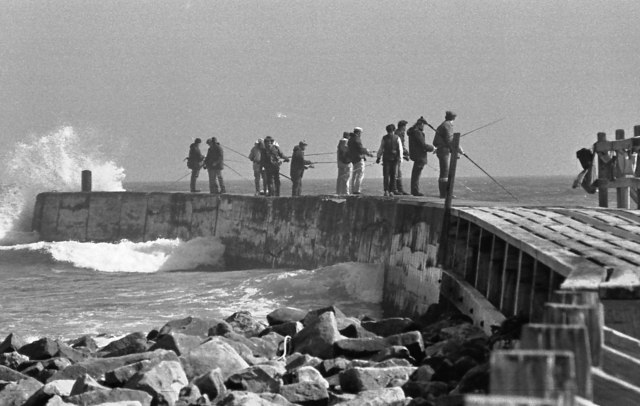 Anglers on the breakwater and incoming tide