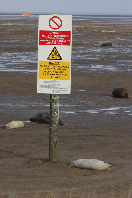 Warning sign and grey seals at Donna Nook