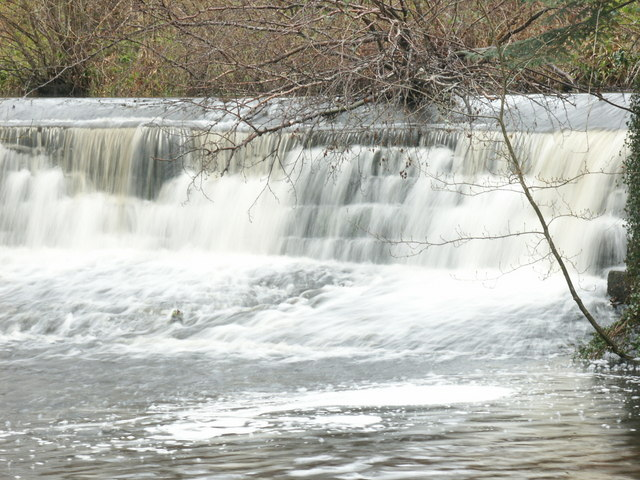 Water flows over dam on the Waren Burn at Twizell Mill