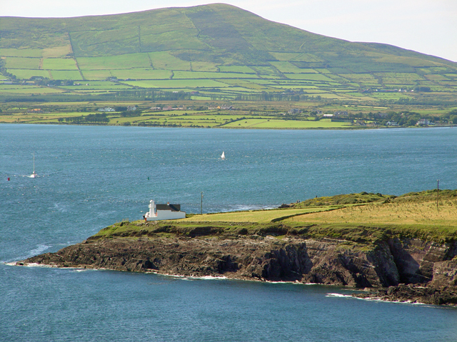 Cliffs and lighthouse before Dingle Bay