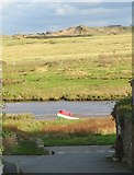 SH3568 : Painted in the national colours - a boat beached on the west bank of Afon Ffraw by Eric Jones