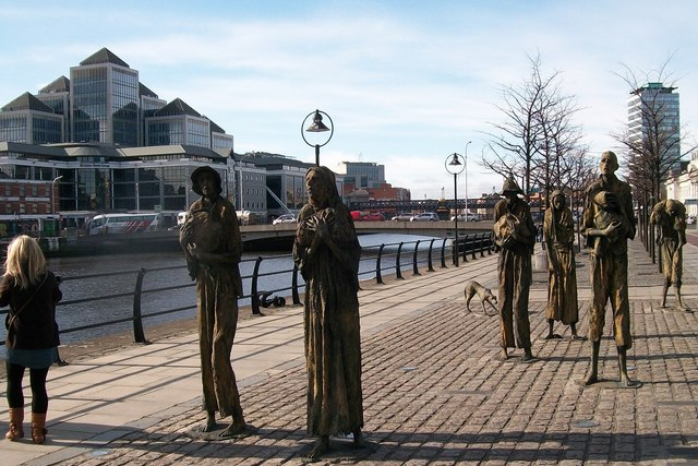 Surrounded by signs of economic progress - the Famine Memorial on Custom House Quay