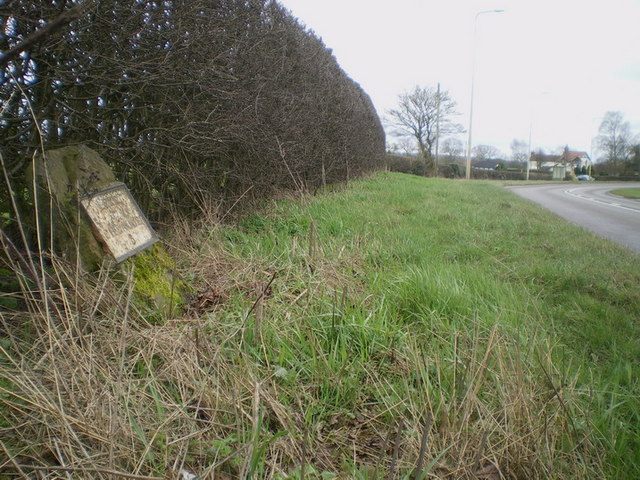The Greenhead milestone in its setting beside the A52