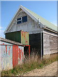TM4599 : Boatyard sheds beside the path onto The Island by Evelyn Simak