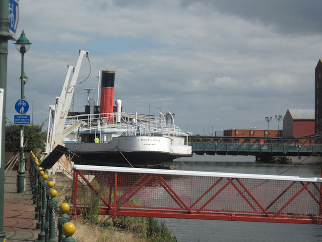 Image shows the white painted stern of a paddle steamer with a red painted smoke stack and white railings.
