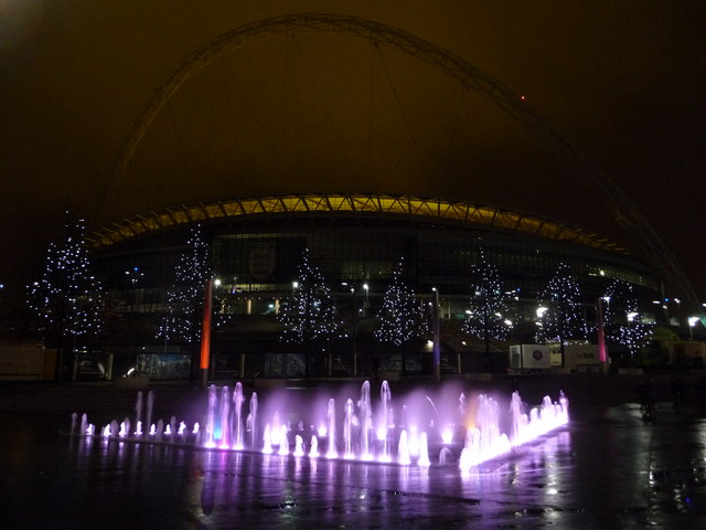 Wembley: fountain, trees and stadium by night