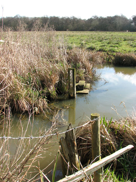 Water level gauge board by derelict pumphouse