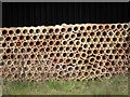 TL1381 : A stack of drainage tiles by Michael Trolove