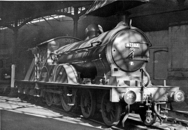 Shafts of sunlight strike a North Eastern D20 4-4-0 inside Gateshead Locomotive Depot