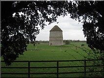 SK7645 : Sibthorpe dovecote seen between the churchyard yews by Jonathan Thacker