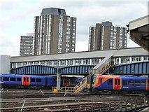 TQ2775 : Trains under the footbridge, Clapham Junction by Christine Johnstone