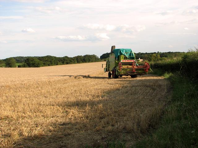 Combine harvester in field by Saxlingham Road, Blakeney