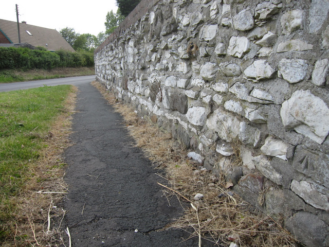 Wall alongside Lighthouse Road, and a bench mark