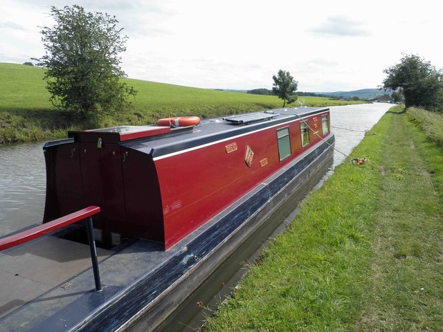 Silsden boats Gwen's Drum moored near a winding point on the Leeds Liverpool canal.