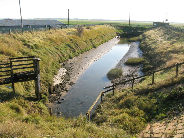 Drainage ditch leading to an outfall under nearest bank