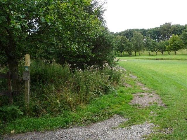 Waymark at golf course hedge