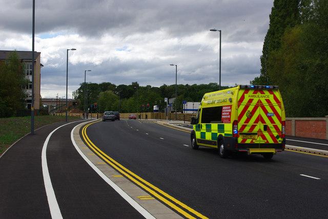 An ambulance speeds along Aston Webb Boulevard, Bournbrook