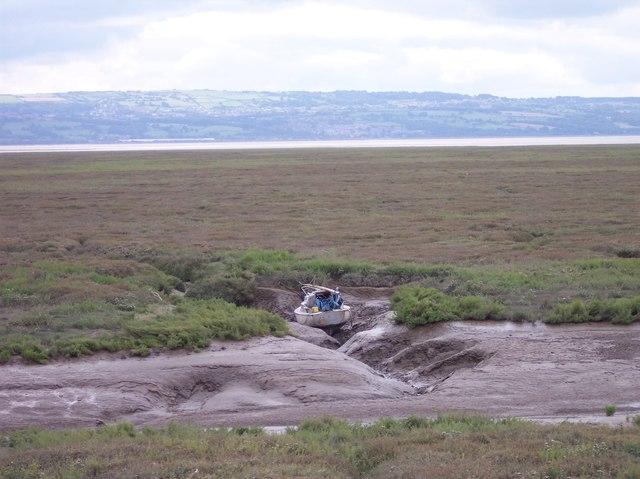 Boat in muddy creek of  the Dee salt marsh