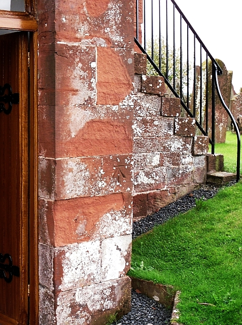 Benchmark by church door