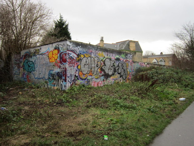 Graffiti filled wall beside the old rail line