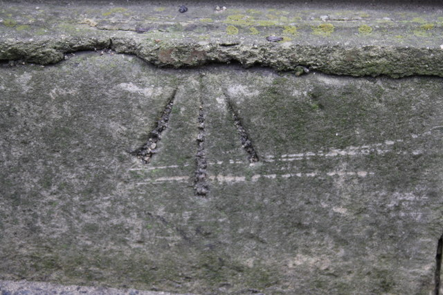 Benchmark on low wall in front of house, New Road