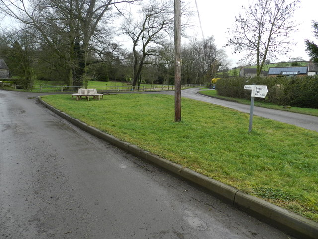 A triangle of grass, with restored bench