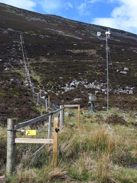 Wind-powered electric fence rising on heather slope
