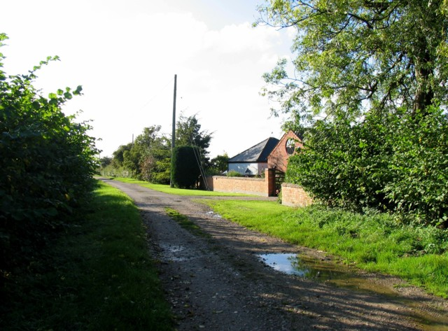 Six Hills Road westwards past the entrance to Meadow View