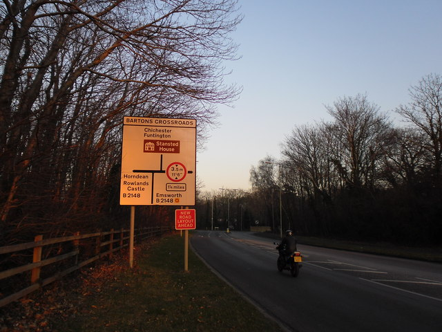 Motorcyclist passing a road sign in Bartons Road