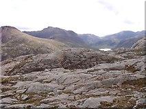 NG9981 : Rocky ridge of Creag-mheall Mor by Sally