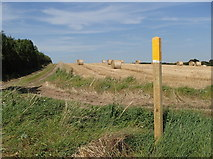 SK7260 : Field with bales, and footpath marker by Andrew Hill
