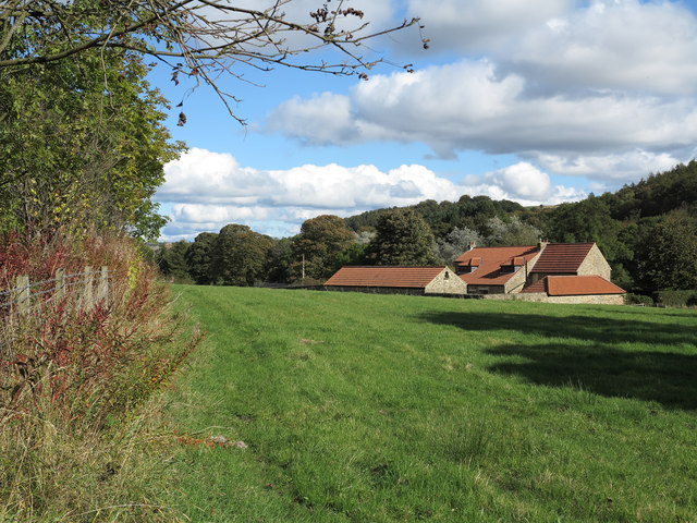 House with outbuildings across field