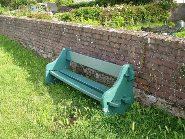 Green seat against the wall to the allotments
