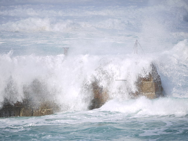 Waves crashing over the jetty at Sennen cove