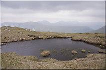 NN2323 : Small lochan on the summit of Meall nan Tighearn by Iain A Robertson