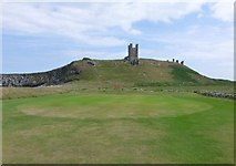 NU2522 : The 'well-defended' 13 green on Dunstanburgh Castle Golf Course by Russel Wills