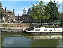 TQ3882 : Boat on Limehouse Cut with Three Mills and the River Lea beyond by David Martin
