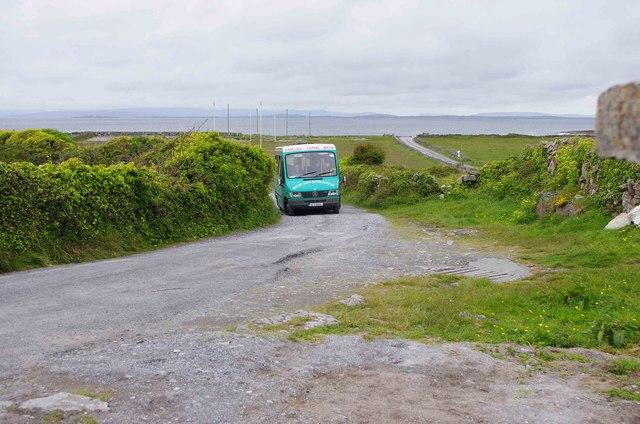 Minibus approaching Na Seacht dTeampaill (Seven Churches), near Onaght, Inishmór (Árainn), Aran Islands, Co. Galway
