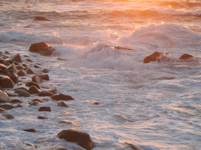 Rock and breakers at sunset in Sennen Cove