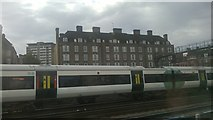 TQ2878 : South of Victoria station: Peabody Estate flats seen over a Brighton train by Christopher Hilton