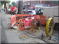 TQ2385 : Hole in the road, Cricklewood Broadway by David Howard