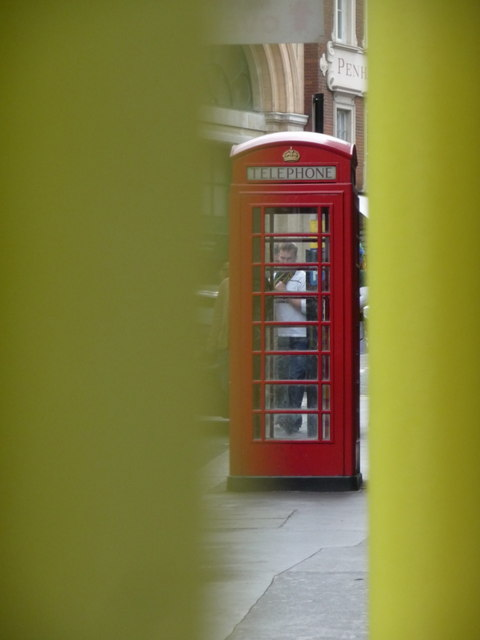 London: red phone box between two yellow poles