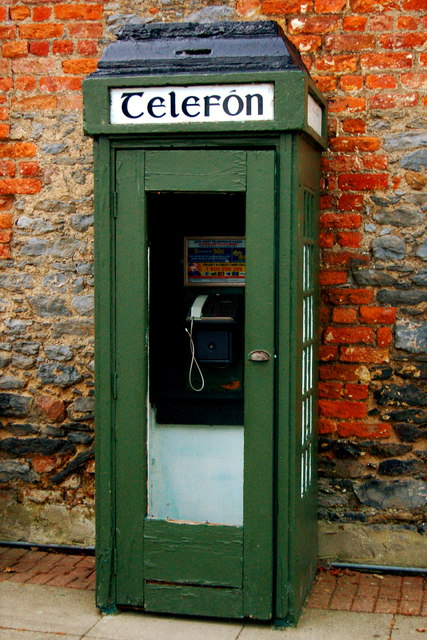 Bunratty - green Telefon booth against grey stone and red brick building