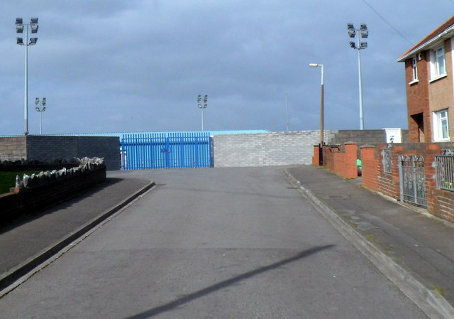 Blue gates and floodlights at the eastern edge of the Remax Stadium in Port Talbot