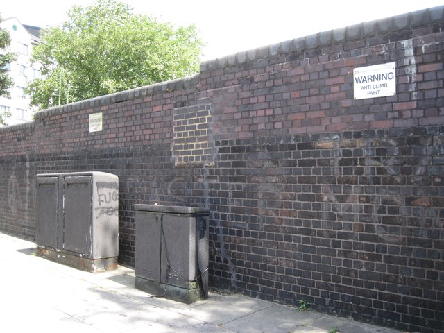 Brick wall with signs warning of 'anti climb paint', north end of Harewood Avenue
